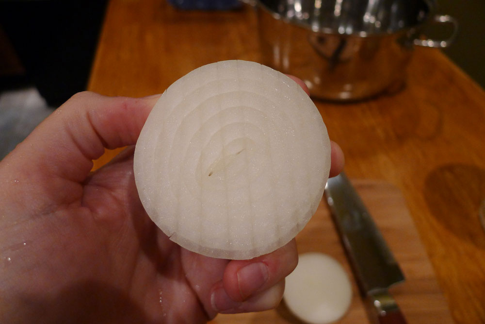 Cut an onion in half, then score it vertically, cutting in only about 1/2 inch deep